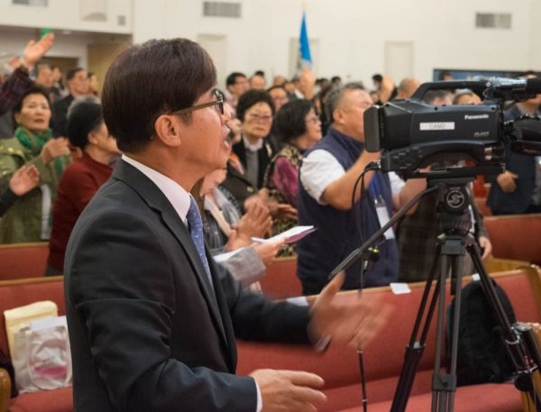 Rev. Sam Shin worships with around 400 people at a world education missions conference held at Young Nak Presbyterian Church on February 1, 2018