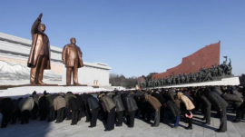People bow down to Kim Il Sung and Kim Jong Il statue. It was built on the site of Jang Dae-hyun's church, a symbol of revival in Pyongyang