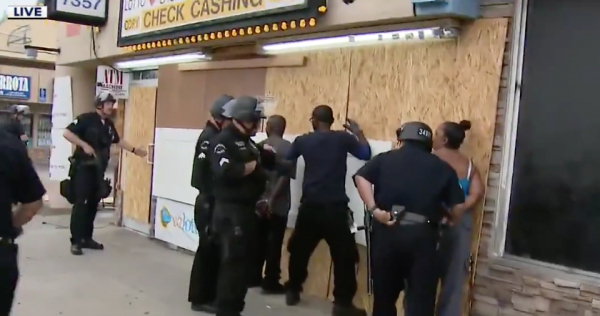 African American business owner handcuffed while the police officers are confused.