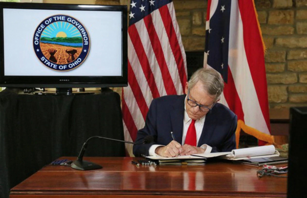 Mike DeWine signed legislation Wednesday curbing his power to change Ohio elections and close houses of worship in the state.