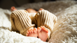anonymous barefooted baby sleeping on soft bed in sunlight