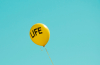 yellow 'Life' printed balloon