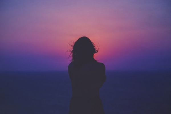 Woman facing sunset in Rhodes, Greece