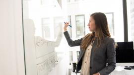 woman writing in whiteboard in school