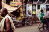 man holding commuter bike in a street in Varanasi, India
