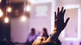Christian raising hand in worship of God in church