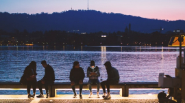 People sitting on a bench beside water