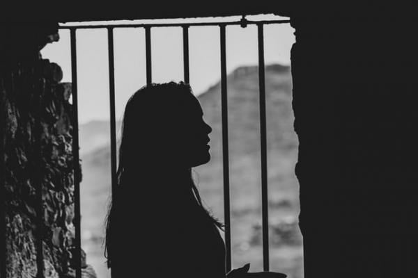 woman female inside prison cell standing beside gates