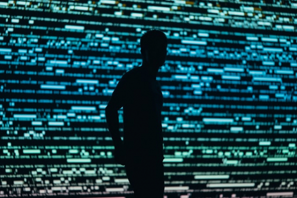 silhouette of a man standing in front of a huge display