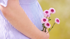 pregnant mom holding flowers near her tummy
