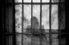 anonymous person behind bars in jail prison