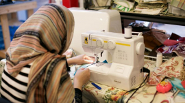 photo of refugee working with a sewing machine on a project.Peace of Thread