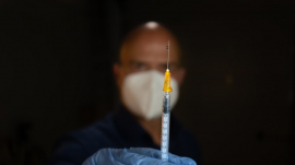 syringe held in hand by man wearing mask and gloves