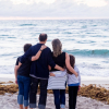 family of four standing on the beach facing the sea