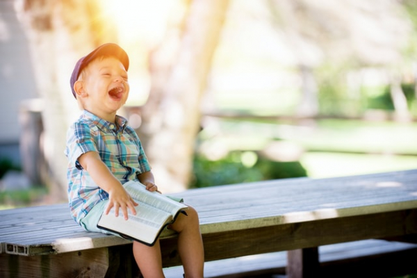 Child reading a Bible laughing happy life