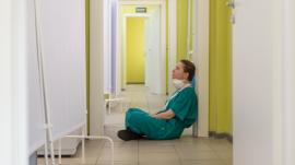 medical health worker sitting on the floor in hospital corridor