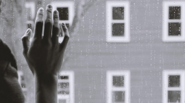 hand touching a glass panel window indicating a longing to go out and socialize with others