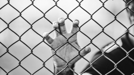 man holding chainlink fence with hand