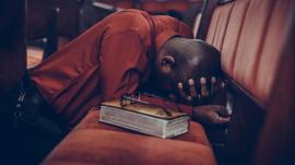 man in church kneeling in prayer