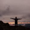 man raising hands worshiping God beneath a dark gloomy sky