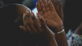 hands raised in prayer and worship in church