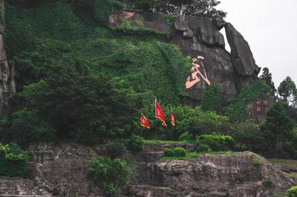 rock wall / mountain face with a huge Chinese letter inscribed on it and red flags in front