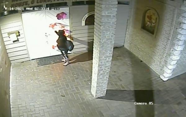 hooded woman setting church door on fire