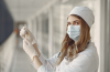 woman doctor in medical garb and mask holding an injection