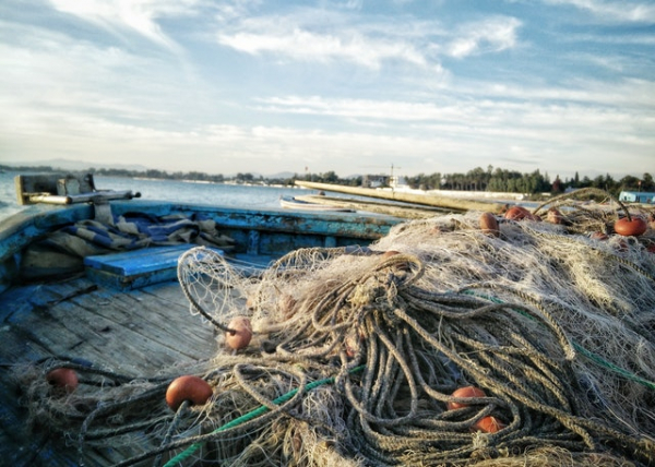 fishing boat with nets scattered around