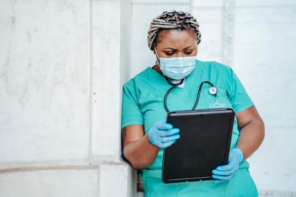 nurse in scrubs holding a file