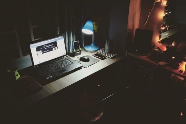 laptop computer in table being used in a dark room at night