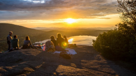 young people having a picnic while looking at the sunset