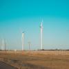 white windmills on a wind farm beside an asphalt road