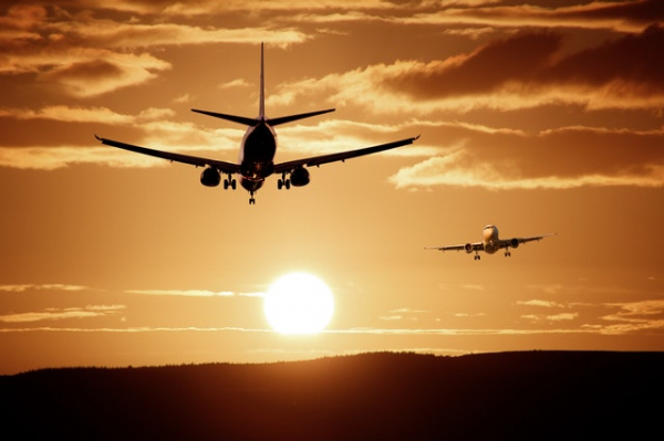 silhouettes of planes in flight towards the sunset