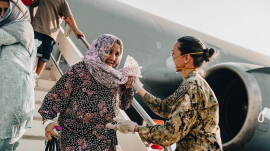Female Afghan refugee assisted by female soldier