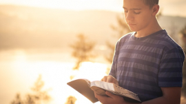 youth reading his Bible outdoors