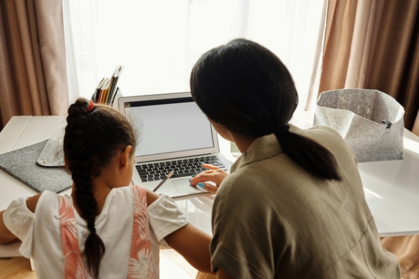 mom teaching her daughter lessons at home