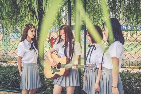 four Chinese women singing and playing the guitar in school