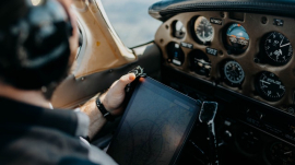 airplane pilot holding iPad while preparing for flight