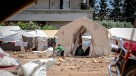 Temporary migrants' tents on ground in daylight