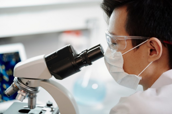 medical technologist examining a sample using a microscope