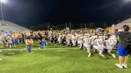 Upperman High School and Stone Memorial High School football players leading the community in a post-game prayer