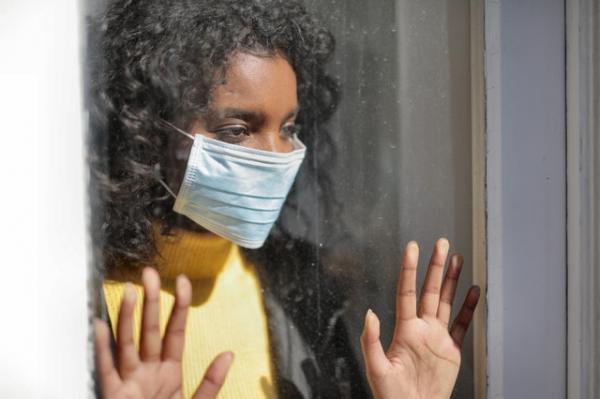 woman wearing mask inside room behind glass window