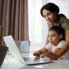 mom helping daughter using laptop computer for home study
