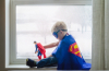 Young boy wearing Superman costume playing with Superman toy