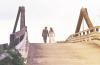 newlywed couple walking hand in hand on bridge